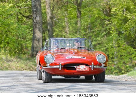 STOCKHOLM SWEDEN - MAY 22 2017: Red Jaguar E-Type classic car from 1966 driving on a country road in the public race Gardesloppet in the forests at Djurgarden Stockholm Sweden. May 22 2017