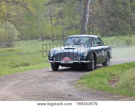 STOCKHOLM SWEDEN - MAY 22 2017: Black Aston-Martin Saloon classic car from 1965 driving on a country road in the public race Gardesloppet in the forests at Djurgarden Stockholm Sweden. May 22 2017