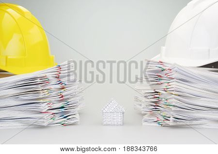 House between pile overload document of report and receipt with colorful paperclip have yellow and white engineer hat on top with white background.