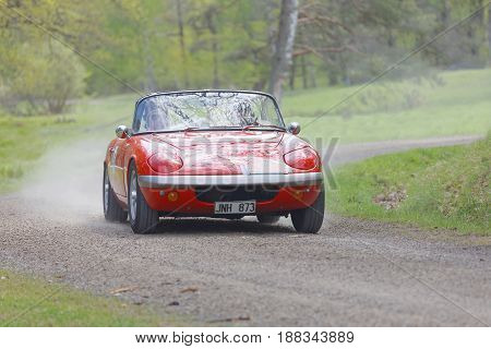STOCKHOLM SWEDEN - MAY 22 2017: Red Lotus Elan classic car from 1966 driving on a country road in the public race Gardesloppet in the forests at Djurgarden Stockholm Sweden. May 22 2017