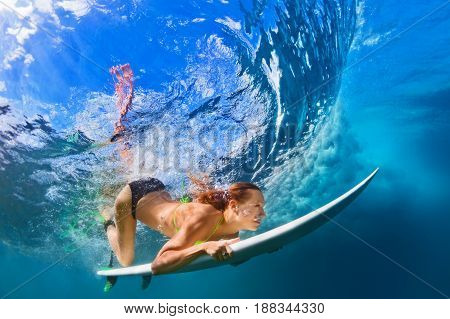 Active girl in bikini in action. Surfer woman with surf board dive underwater under breaking big wave. Healthy lifestyle. Water sport extreme surfing in adventure camp on family summer beach vacation