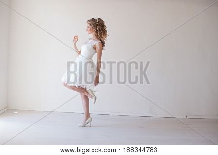 girl in a wedding dress stands in a white room wedding legs