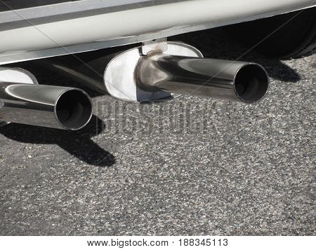 Closeup of a classic car exhaust pipe . Double pipe . Pollution concept