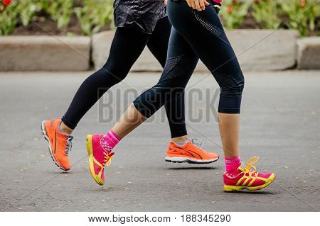 two young girls running street in bright running shoes