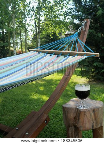 Hammock in the Shade. A colorful garden hammock rests in the shade with a cold beverage nearby