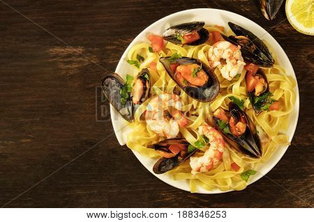 A photo of a ready to eat seafood pasta dish with mussels and shrimps, shot from above on a dark wooden rustic background texture, with a place for text