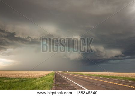 A powerful supercell thunderstorm looms over the highway in eastern Colorado.