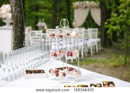 Delicious sweet cupcakes and candies, decorated in wedding style on special support, in front of wedding archway