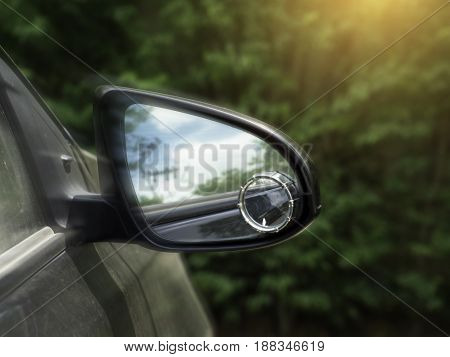 Car side mirror for rear view with traffic reflection background.