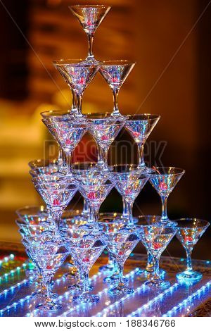 Pyramid of holiday shiny wineglasses with wine or champagne. Selective focus