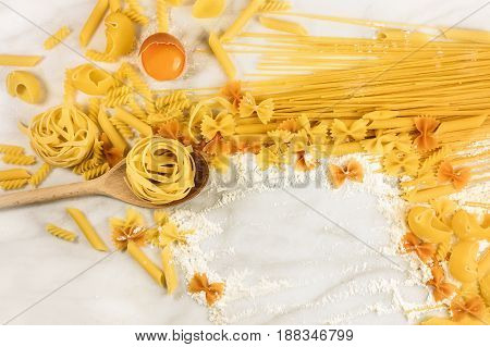 Various types of pasta on a white marble table with an egg and flour, forming a frame for copy space