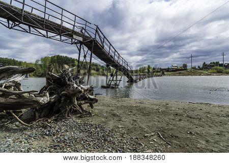 An old pontoon bridge across the river. Russia, Siberia, the Razdelnaya River, Novosibirsk Region.
