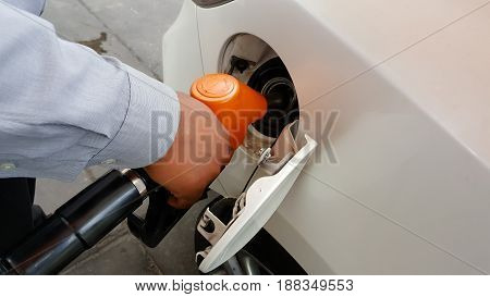 Hand refilling the car with fuel and  background