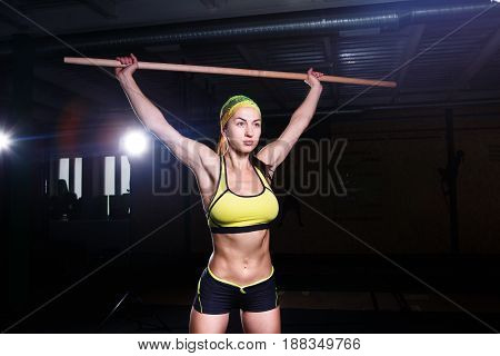 Young Beautiful Girl Is Exercising In The Gym. Holds A Stick Over His Head For Trinorvki Muscles Of