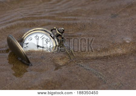 round clock with hands lying on the wet sand under water time