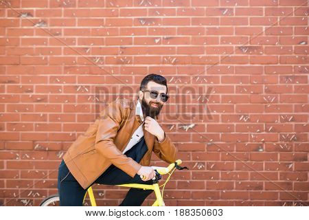 Young Handsome Man With A Beard Against Brick Wall Sits On A Bicycle