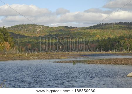 Cloud shadows crossing hills bordering New Hampshire pond