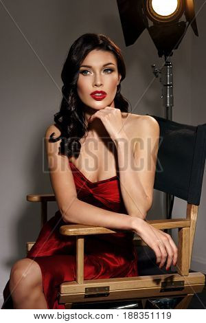 Young pretty beautiful woman in red long evening dress with makeup, red lips and classical hollywood waves hairstyle sitting in director's chair at film set with two cinema lights.