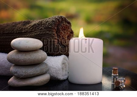 Spa still life with towels, a burning candle, bath oil and massage stones against the backdrop of a green garden.