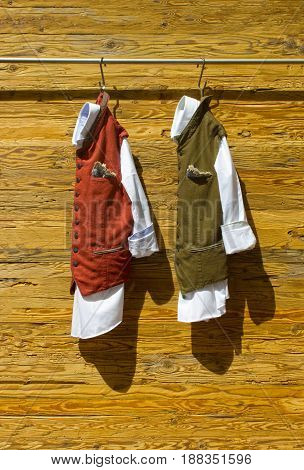 National styled male suits in Salzburg at Austria on wooden background