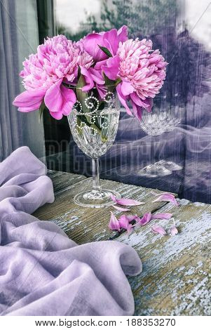 Bouquet of pink peonies on a wooden surface in vintage style.