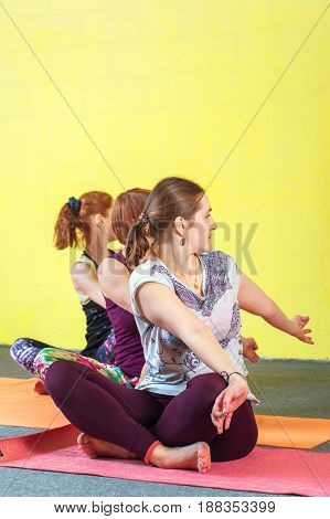 Group of middle aged caucasian women practicing yoga in class. Three female adults working out. sitting in meditation position. Fitness and healthy lifestyle. Body balance training.