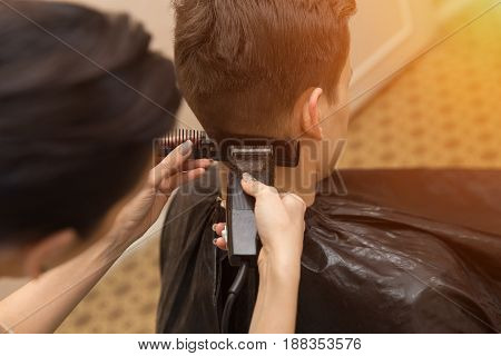 Portrait Of Handsome Man In Barbershop. Barber Working With Electric Razor