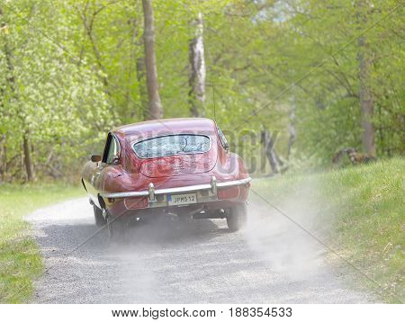 STOCKHOLM SWEDEN - MAY 22 2017: Rear view of purple Jaguar E-type Ser2 classic car from 1970 driving on a country road in the public race Gardesloppet in the forests at Djurgarden Stockholm Sweden. May 22 2017