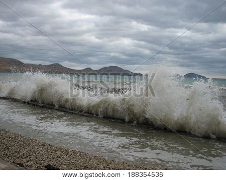 Big wave beating with splash in a cloudy storm weather, feeling of freedom