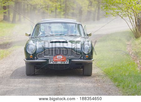 STOCKHOLM SWEDEN - MAY 22 2017: Green Aston Martin DB6 classic car from 1970 driving on a country road in the public race Gardesloppet in the forests at Djurgarden Stockholm Sweden. May 22 2017