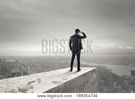 Businessman looks at the city from the roof above the city