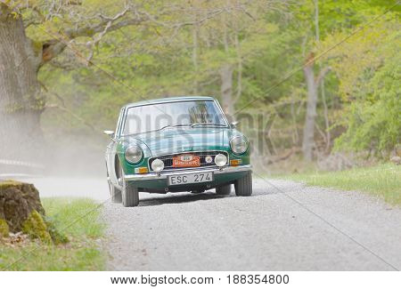 STOCKHOLM SWEDEN - MAY 22 2017: Green MGB 1800 GT classic car from 1970 driving on a country road in the public race Gardesloppet in the forests at Djurgarden Stockholm Sweden. May 22 2017