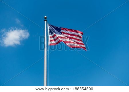 A photo of the American flag on a long pole with blue sky behind.