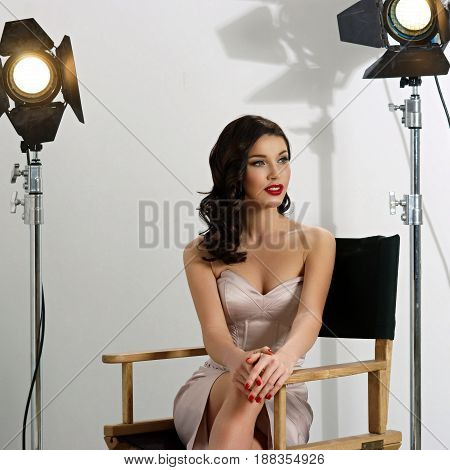 Young pretty beautiful woman in elegant dress with makeup, red lips and classical hollywood waves hairstyle sitting in director's chair at film set with two cinema lights.