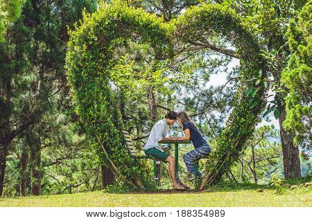 A Loving Couple Under A Bush In The Form Of A Heart. St. Valentine's Day, Love Concept