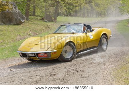 STOCKHOLM SWEDEN - MAY 22 2017: Yellow Chevrolet Corvette Stingray classic car from 1971 driving on a country road in the public race Gardesloppet in the forests at Djurgarden Stockholm Sweden. May 22 2017