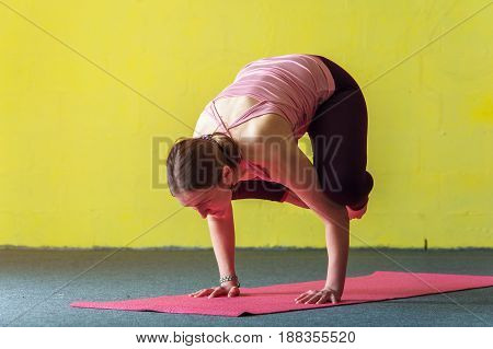 Young woman doing yoga practice against yellow wall. Female performing handstand Asana. Body balance training. Fitness and healthy lifestyle concept.