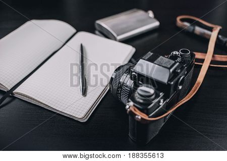 vintage camera and old photos on wooden background. nostalgic style picture