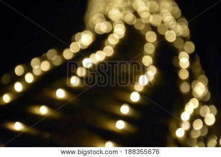 Defocused Bokeh twinkling lights background. Festive background with natural bokeh and bright golden defocused lights.
