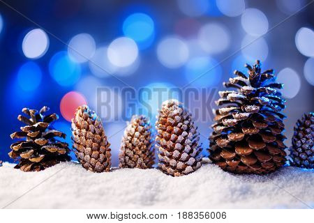 Snowy christmas background with fir and pine cones