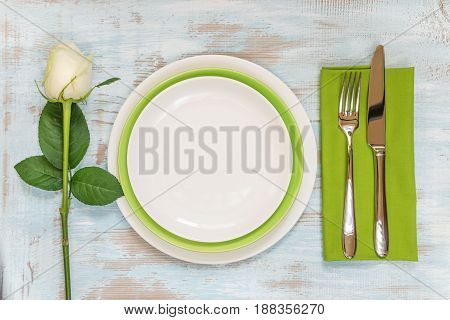 White and green empty plates green linen napkin fork and knife and white rose flower on an old wooden table; top view flat lay overhead view