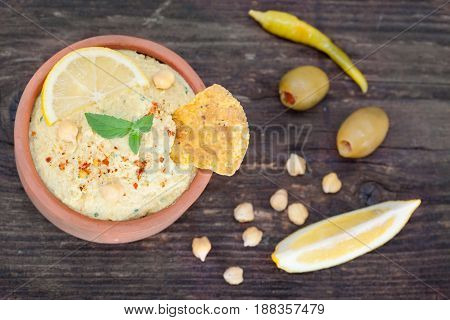 Vegetarian Humus with sesame seeds,tortilla chip, olives and lemon. Top view.