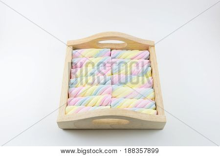 Colorful candy in wood tray on white background.