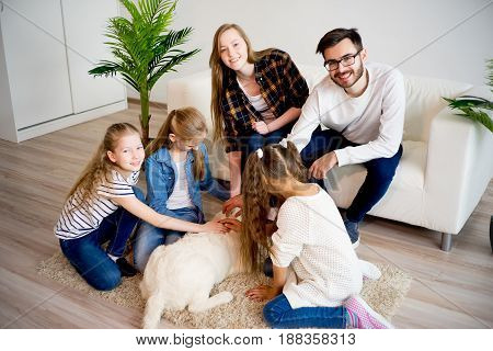 A portrait of a family playing with their dog indoors