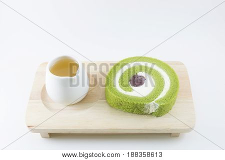 Green tea roll cake on the wooden board.