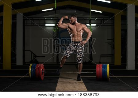 Muscular Man Exercising Back With Barbell In Gym