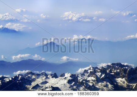 snow-caped mountain peaks and clouds in the distance