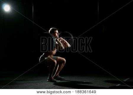 Fitness training. Man doing sit ups with weights in dark gym.
