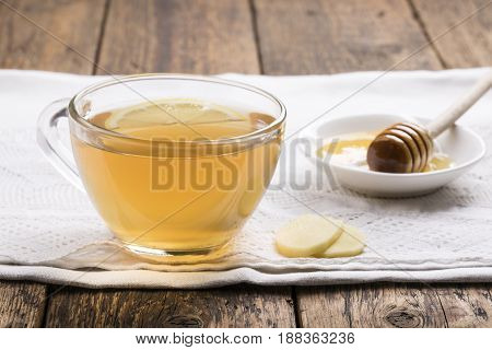 Ginger tea with lemon and honey on a wooden table.