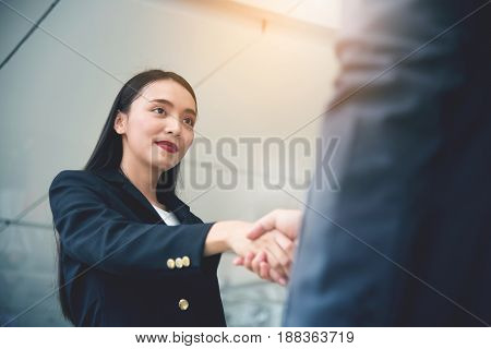 Successful business negotiations with Asian Businessman and Businesswoman. Hands shaking and smiling.